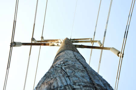 a wooden electrical pole at extreme perspective against a blue sky