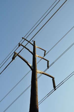 A single wood electrical pole against a blue sky