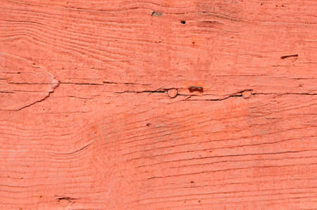 macro of a plank of weathered wood painted red in the sunlight Stock Photo