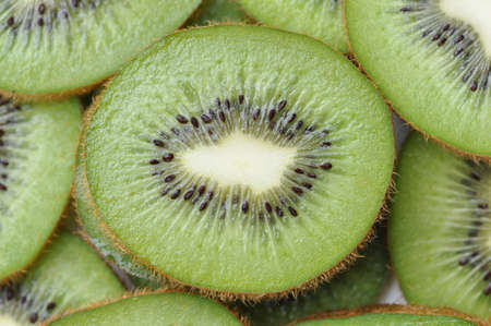 macro of a slice of green kiwi with white center and black seeds