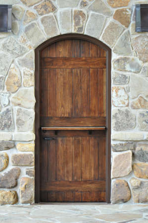 A single wood door set in a natural stone wall and walkway