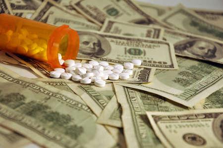 A prescription bottle of white pills spilling on a pile of $100 dollar bills Imagens