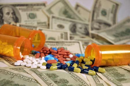3 bottles of pills spilling over a pile of one hundred dollar bills  Stock Photo