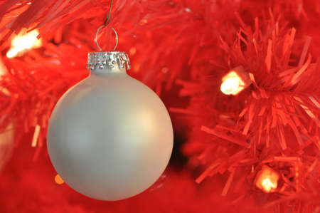 A silver ball ornament against a red background