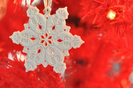 A white snowflake ornament against a red tree background