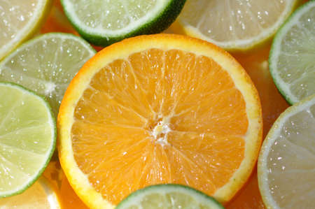closeup of a single bright juicy orange slice in the middle of sliced citrus fruit