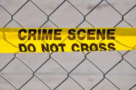 Close up do Crime amarelo brilhante fita Scene Do Not Cruz contra uma cerca de arame Imagens