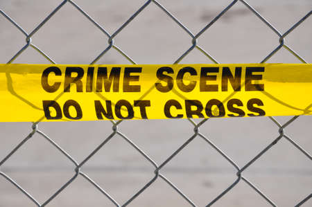 Closeup of Bright yellow Crime Scene Do Not Cross tape against a chain link fence Stock Photo