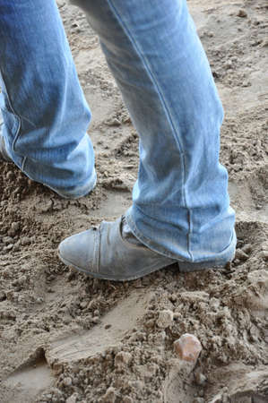 black paddock boots with blue jeans standing in the dirt