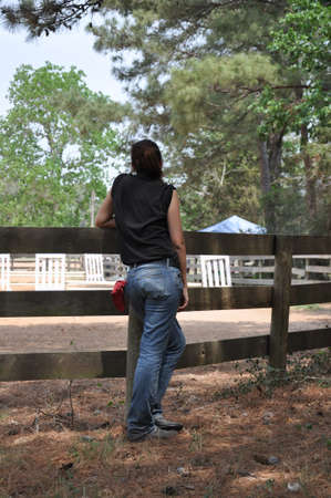 a brown haired woman in jeans with a red rag out of the back pocket standing against a wood fence