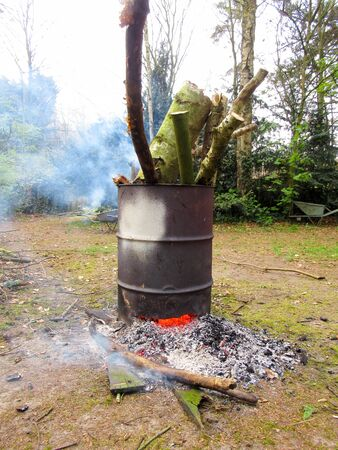 barrel burning excess wood in a clearing or a forrest