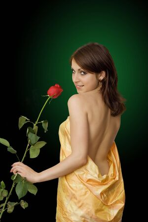 The girl in yellow with a rose flower on a black background Stock Photo - 7934660