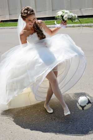 Bride game of football during own wedding photo