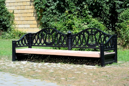 Large bench in the park with cast ornament. photo