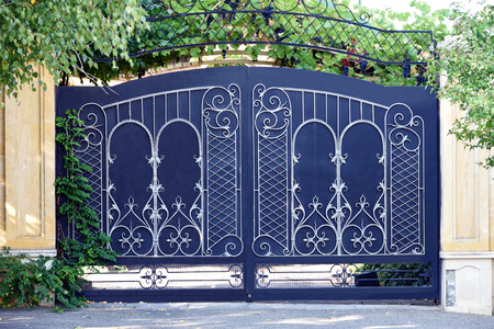 wrought: Forged, matal  gates. Front of the house.
