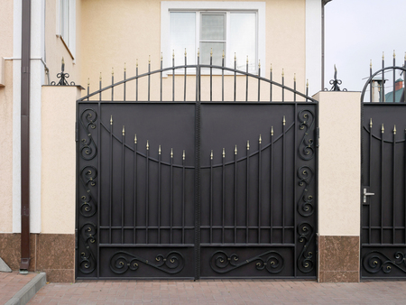 Modern iron gate with wrought-iron decor in the old style.