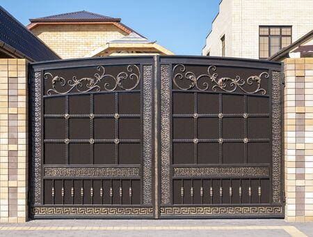 The facade of the house. Modern iron gate with wrought-iron decor in the old style.
