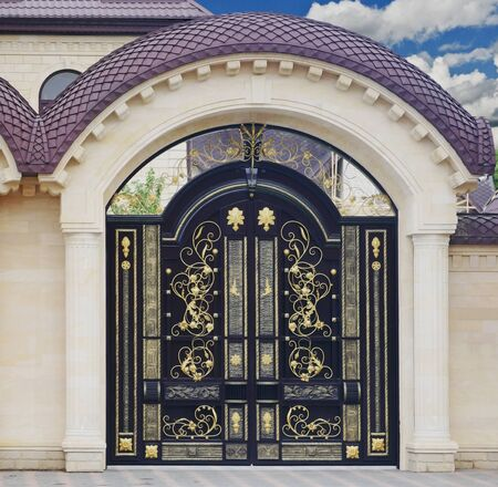 Large forged gate with ornament. The facade of the estate. Stock Photo