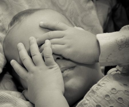 liitle sad baby with hand on face