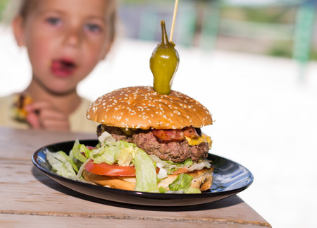 HESITATE: Hamburger on the wooden table with little girl on background