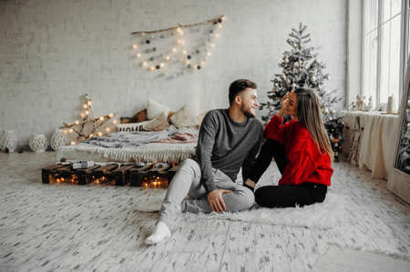 Young couple celebrating Christmas spending time together at home while sitting on the floor. Merry Christmas