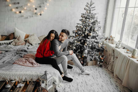 Young happy couple having fun lying on cozy bed and laughing, woman hugging her boyfriend spending winter holidays at home in warm christmas atmosphere