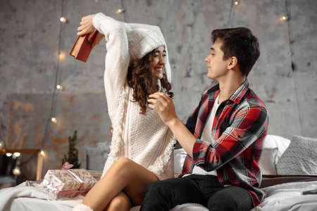Funny couple have fun together while he wants to hit with a book, sit on bed indoor with new year decoration atmosphere, spending Christmas eve. Joyful happy moments in winter holidays. Stok Fotoğraf