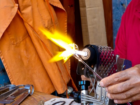 blowtorch: Close up of the hand of a male artisan heating a glass object in the hot flame of a blowtorch.