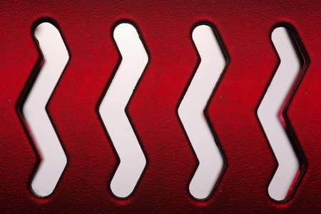 Abstract background of parallel cut out zig zag lines in a red metal surface photo