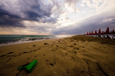 furled: Empty beach resort at sunset under cloudy skies with loungers, furled umbrellas and kids toys.