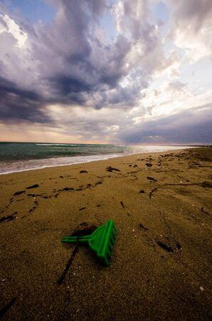 Ciel nuageux sur une plage d�serte au coucher du soleil avec jouets pour enfants abandonn�s couch� dans le sable.