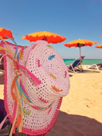 A white straw sunhat in the shade of a beach umbrella on summer beach, holidays