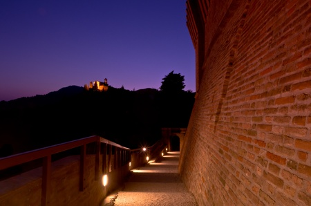 Illuminated empty pathway At twilight leading down between two old brick walls with violet night sky.