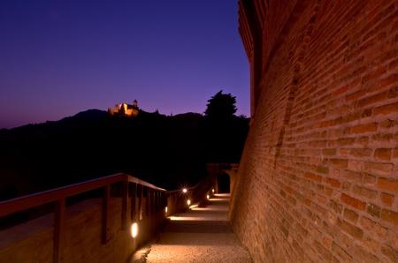 Illuminated voie vide Au cr�puscule qui descend entre deux murs de briques anciennes avec ciel de la nuit violette.
