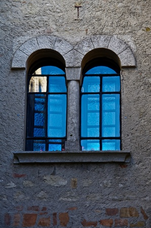 windowpanes: A pair of external arched windows in stonework with turquoise reflection in windowpanes.