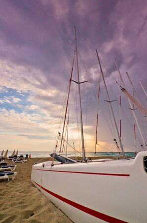 A closeup streamlined biew of a small luxury yacht beached on the sand with a delicate ocean sunset behind.