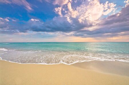 gentle dream vacation: Idyllic empty beach panorama with turquoise ocean, surf and delicate sunset, tropical paradise Stock Photo