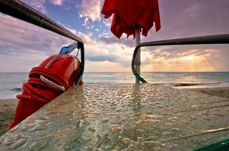 safety googles: Life ring and googles safety equipment supended over the side of a wet deck with ocean sunset beyond. Stock Photo
