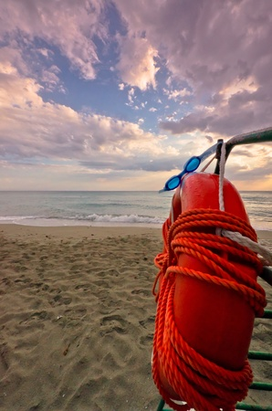 safety googles: A red life ring and safety googles hang on a railing against a sunset seascape.