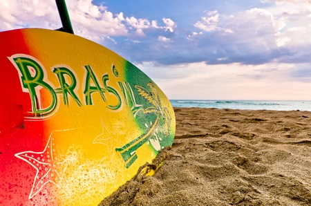 Colourful surboard with Brasil design resting on sandy beach seashore, conceptual tourism and travel.