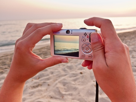caucasian hands holding a small digital camera taking a photo of the beach