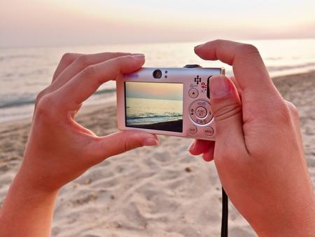 les mains caucasien tenant un petit appareil photo num�rique de prendre une photo de la plage Banque d'images