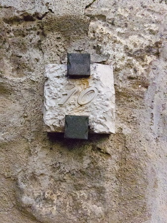 Hewn Stone Plaque Number 10 attached by iron brackets to a stone exterior wall on a residential property. photo