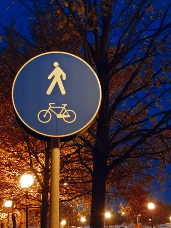 Pedestrian And Bicycle Road Sign At Night illuminated in the glow of streetlamps with an avenue of autumn trees. photo