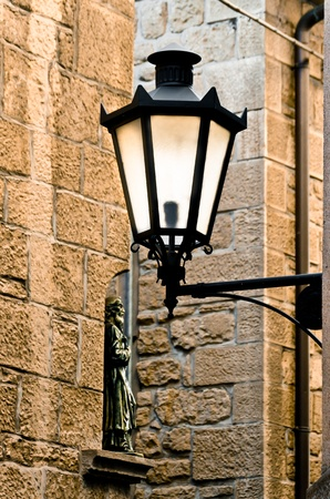 Glowing Wrought Iron Lamp, in traditional lantern shape mounted on wall bracket photo