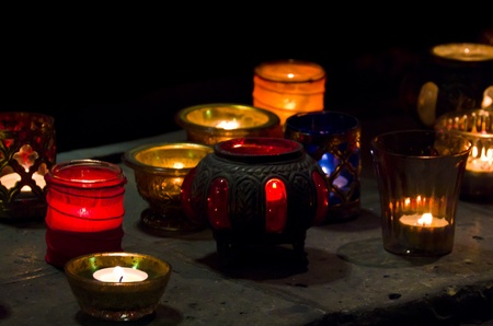 Colourful Glowing Candles in translucent pots in a church or at a celebration.