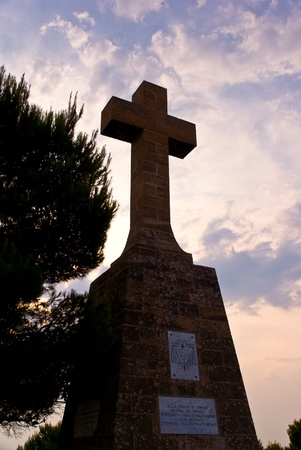 cemetry: Silhouetted Stone Cross against a cloudy evening sky.