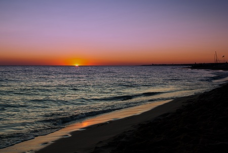 ebb: Beautiful Lavender Ocean Sunset with deep orange glow of the setting sun on the horizon over a deserted beach.