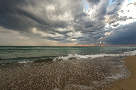 Stormy Skies Over The Ocean with ominous grey clouds and a feint sunset on the horizon. photo