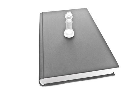 Pi�ce d'�checs en verre sur le livre, un studio isol� abattu sur fond blanc, monochrome